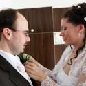 Nevesta pripína pierko svojmu ženíchovi.